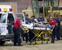 Personnel transport a worker from the site of an industrial accident.