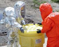 Hazardous Materials team members secure top on drum.